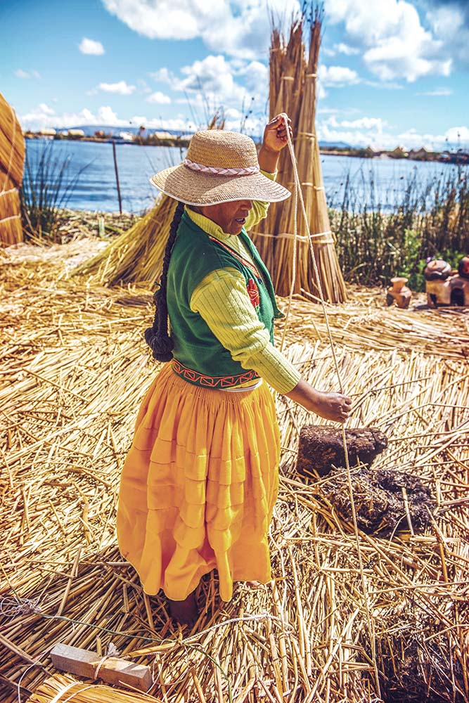 TITICACA, PERU - DEC 29: Indian woman peddling her wares on a re