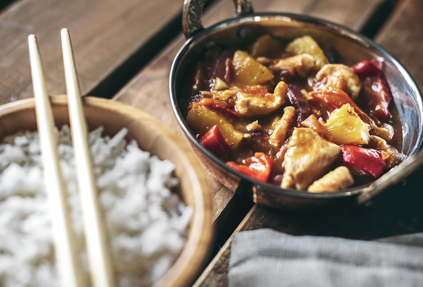 View of Chinese spicy chicken dish and rice in bowl with chopsti