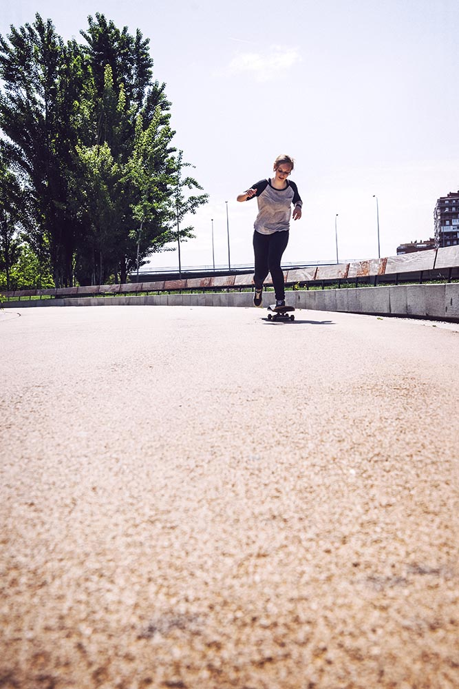 Skateboarder woman practicing ollie at park