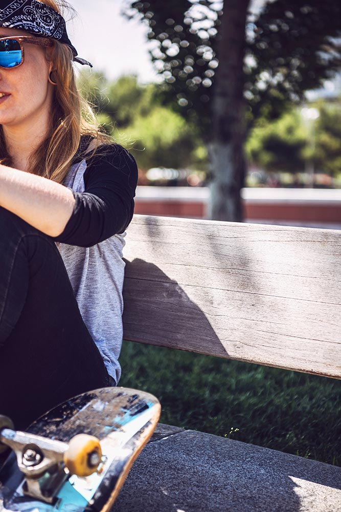 Woman skateboarder sitting in a park