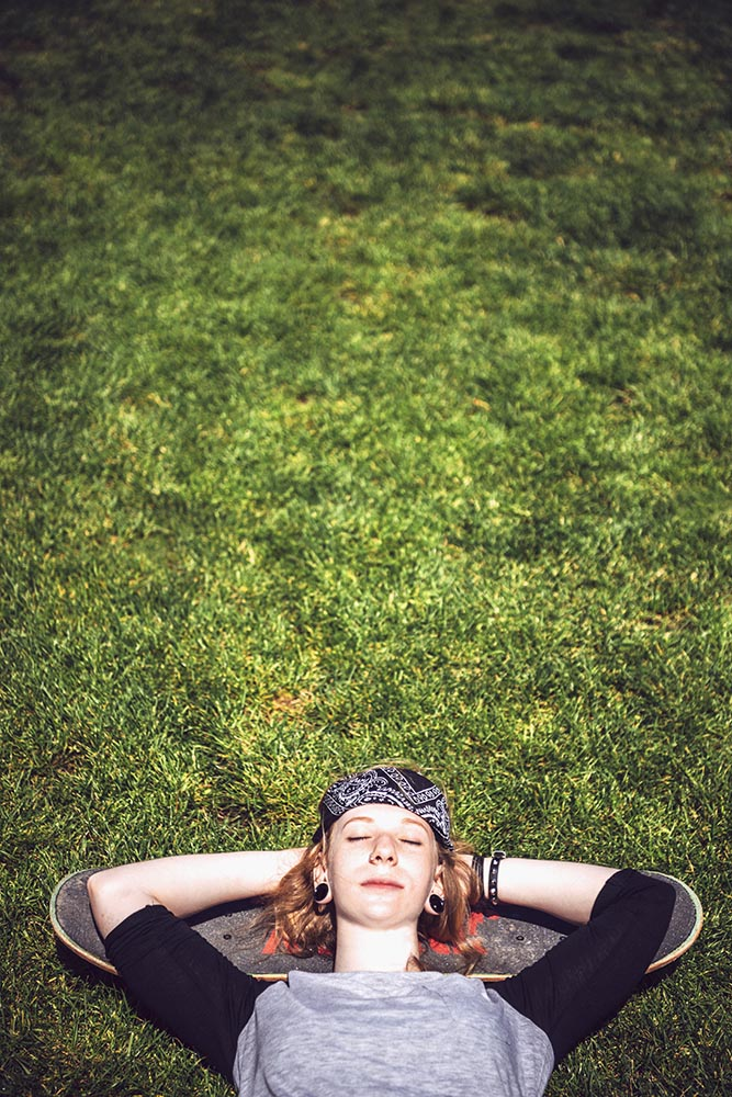 Young woman resting in the grass after practicing skateboard