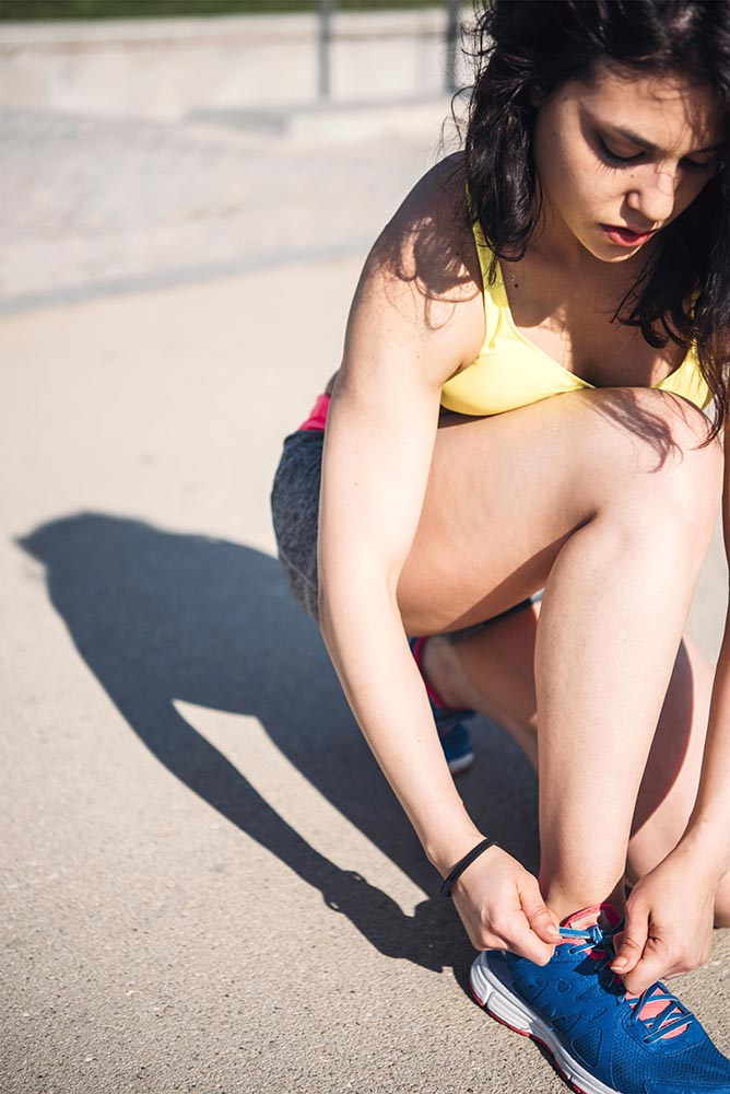 Athletic woman tying the laces on running sneakers