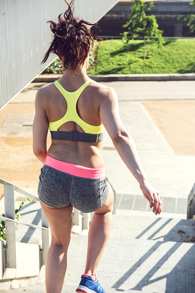 Athletic woman running up stairs during cardio - interval traini