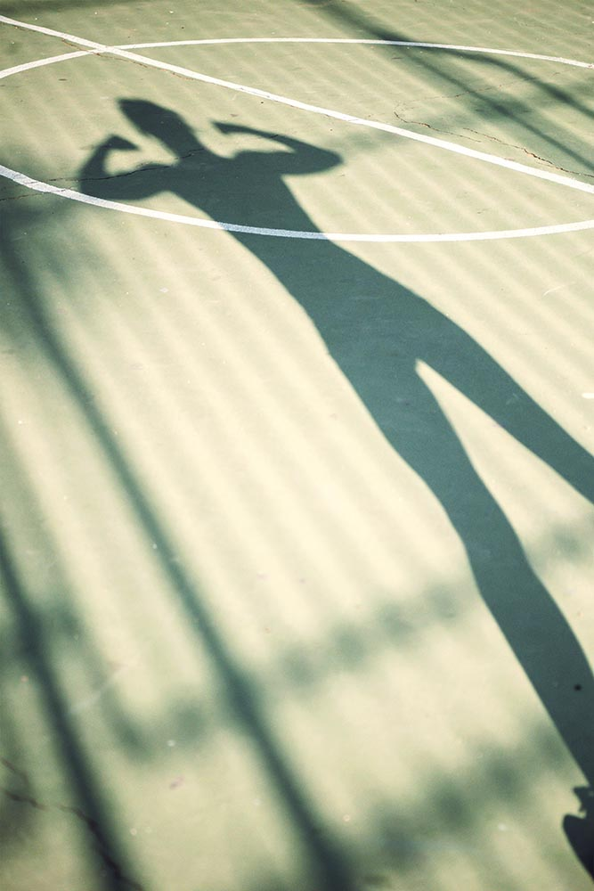 Shadow of running woman on a basketball court