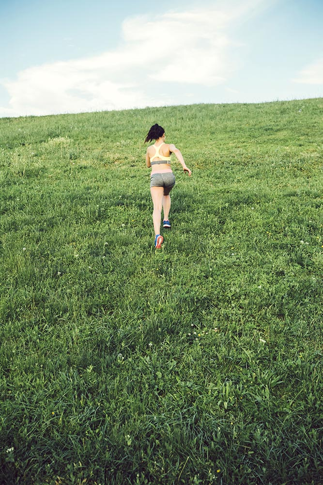 Sporty woman running over a small hill against the skyline