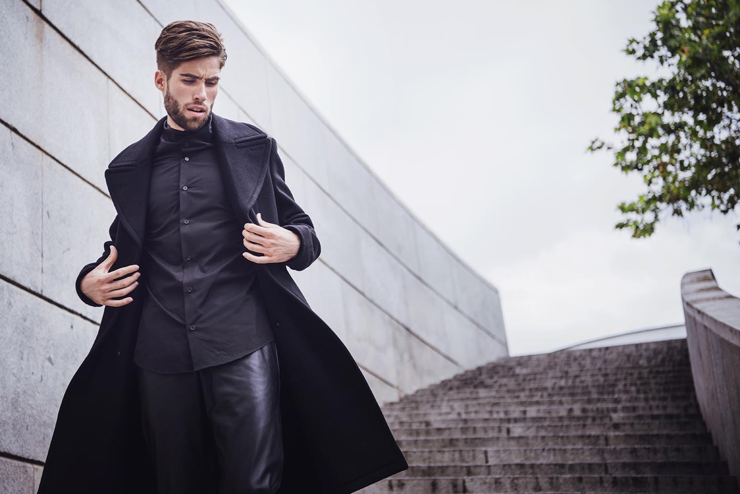 Young handsome trendy man with coat posing on stairs