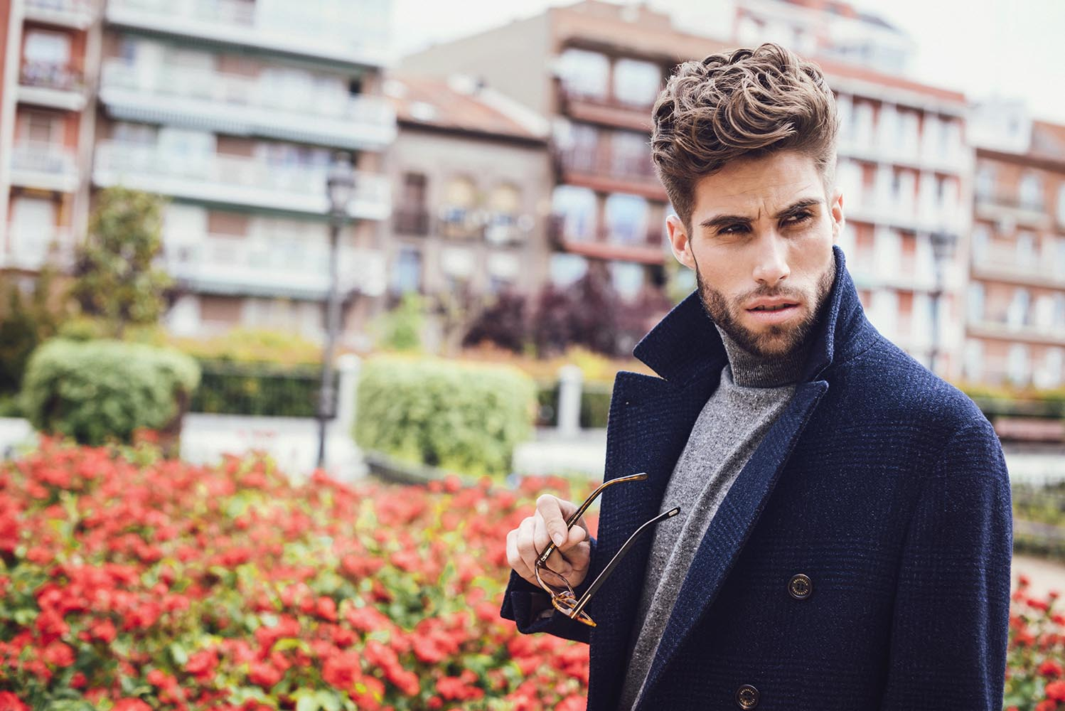 Young handsome trendy man with coat posing with flowers backgrou