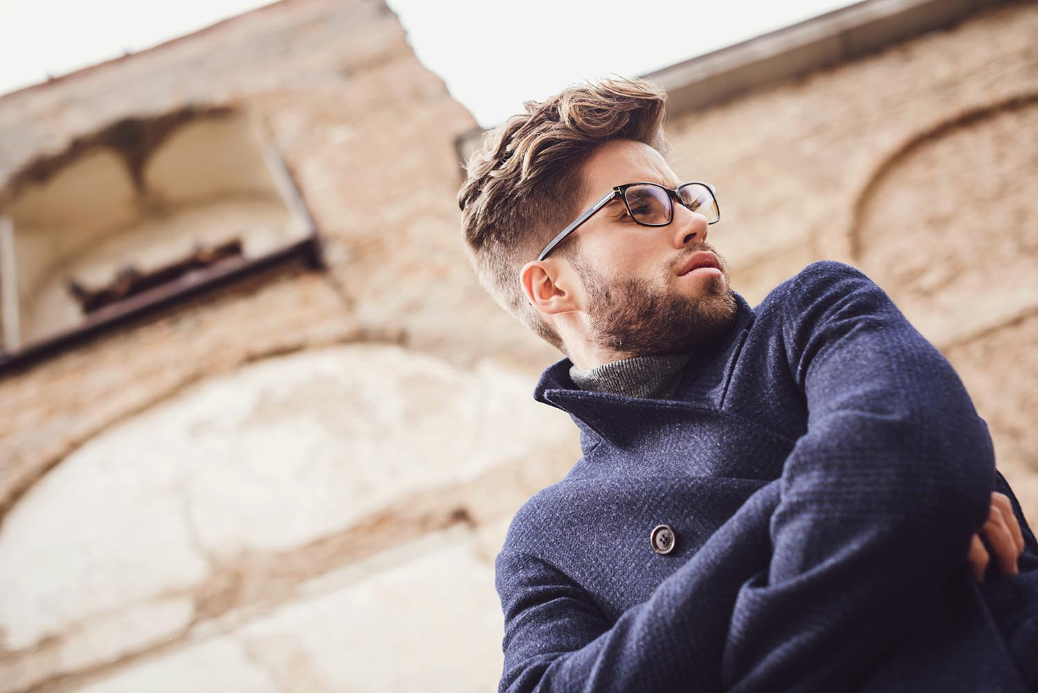 Young handsome trendy man with coat posing with an old wall back