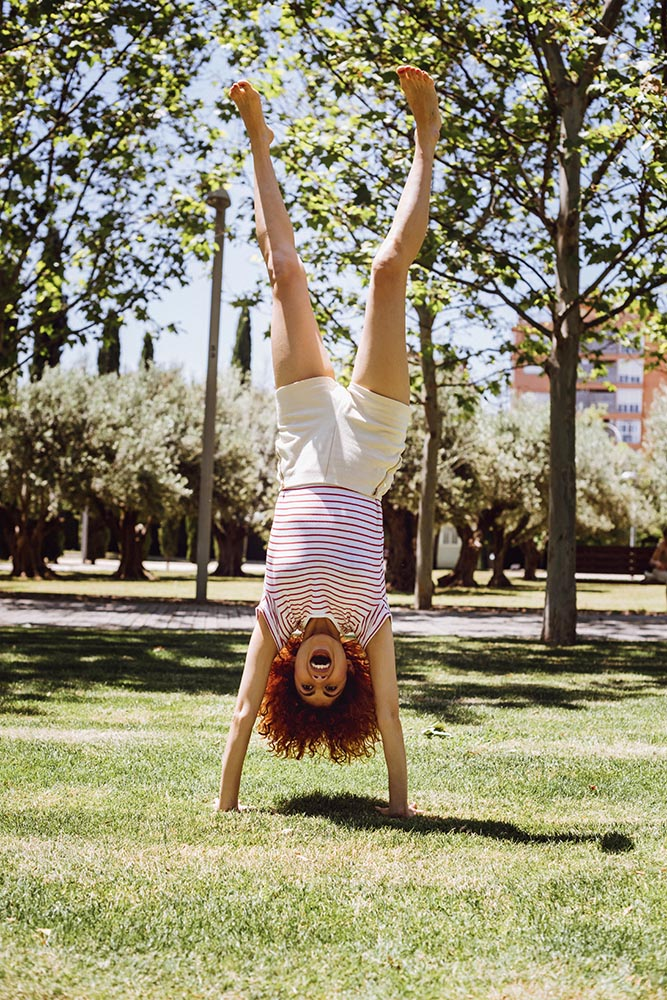 Funny young Woman doing handstand in park in summer