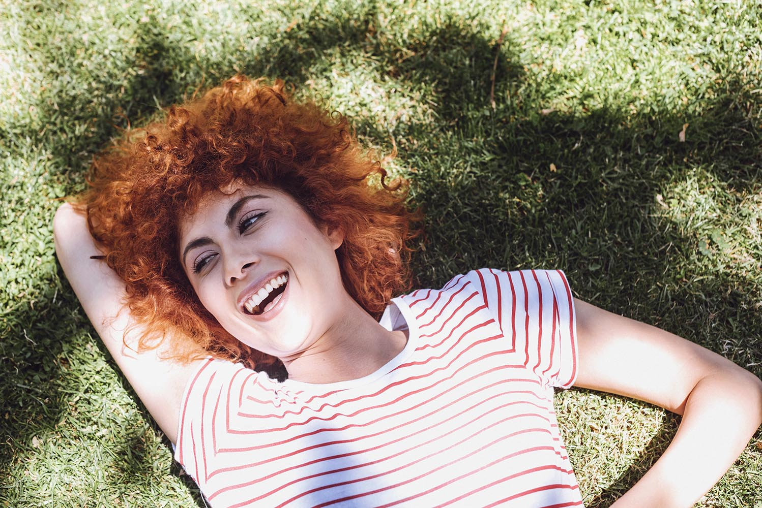 Beautiful young woman lying on grass and laughing