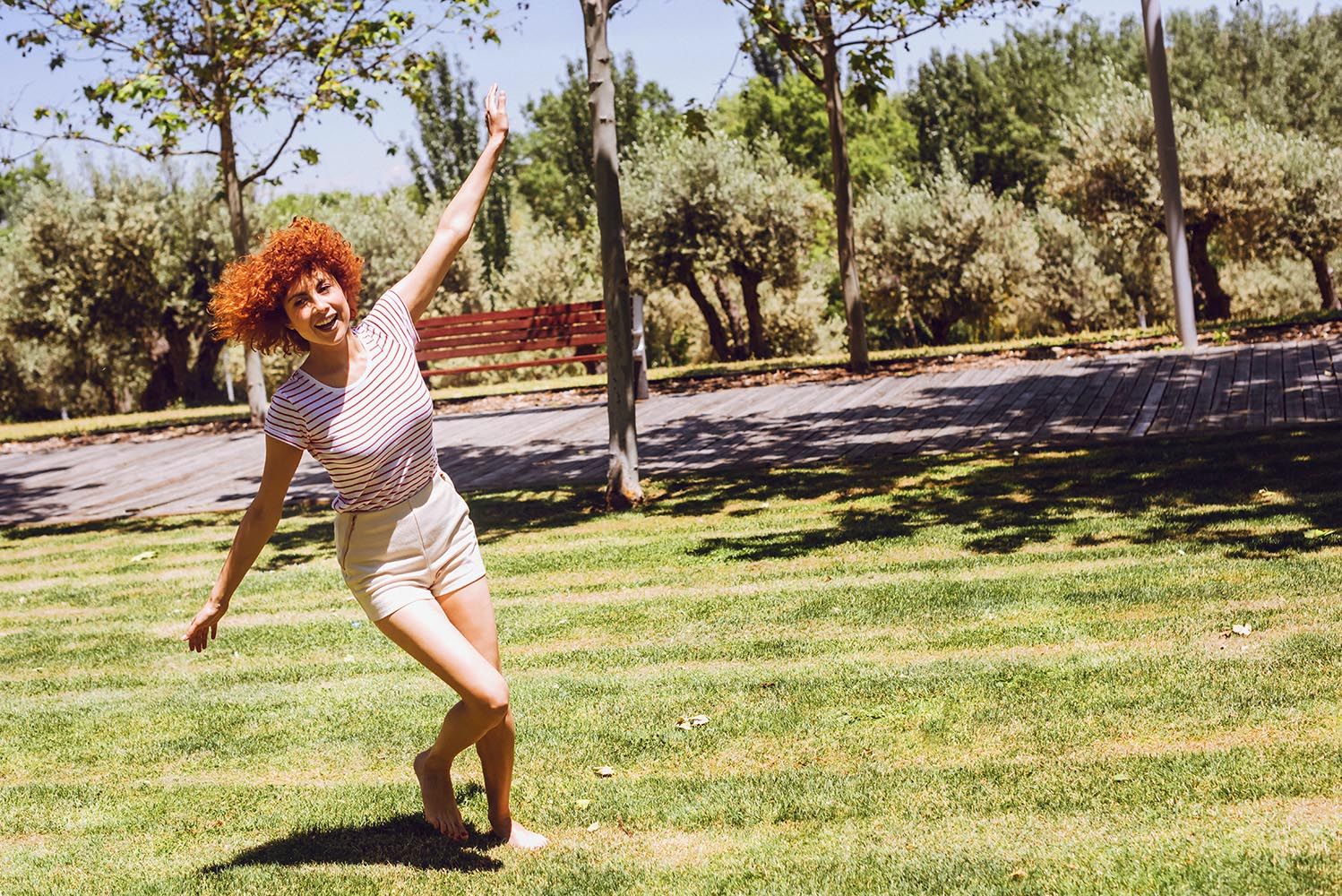 Beatiful woman doing airplane and playing in a park