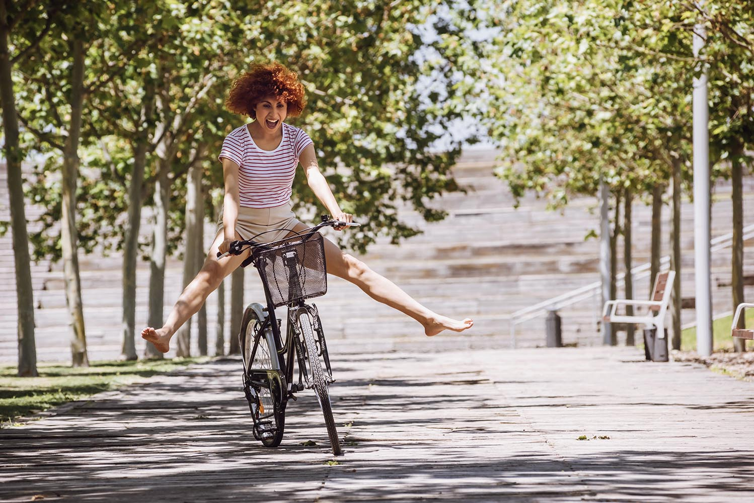 Cheerful girl riding a bike down the street