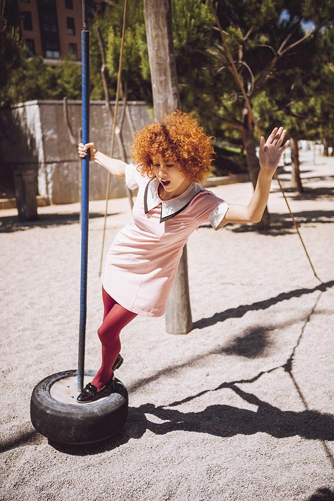 Trendy Young woman playing like a little girl on swings in a par