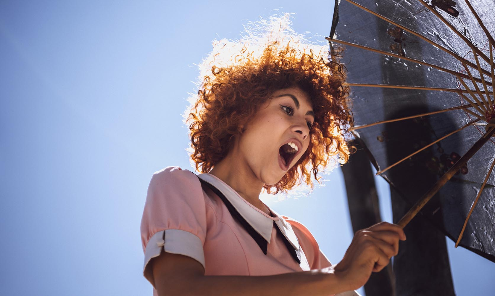 Young woman playing with a chinesse umbrella in a park, having f