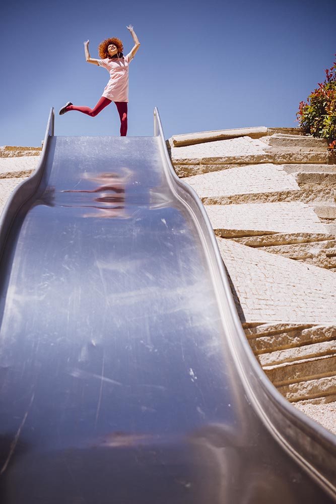Young trendy woman playing in a park on slide