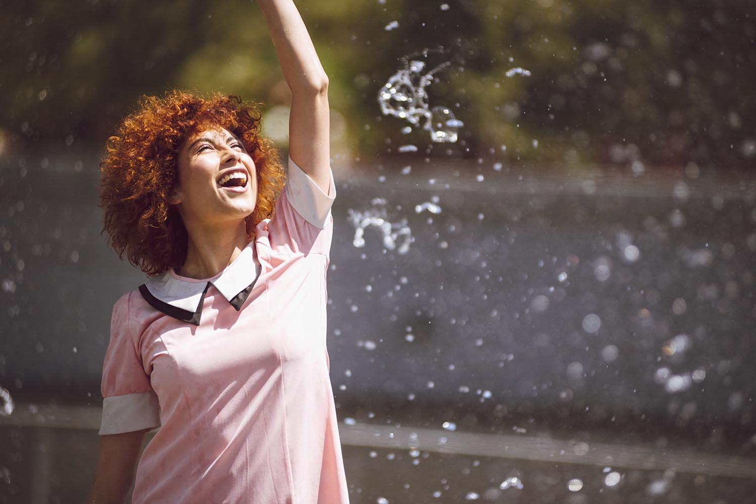 Young beautiful brunette woman playing at outdoor water fountain