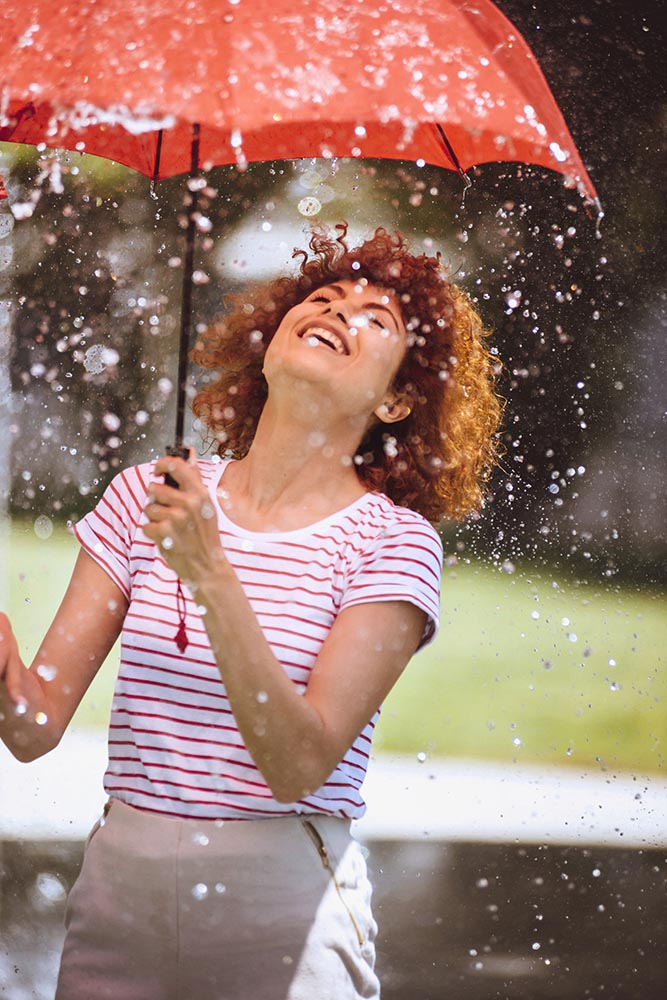 Young beautiful woman playing at outdoor water fountain with an