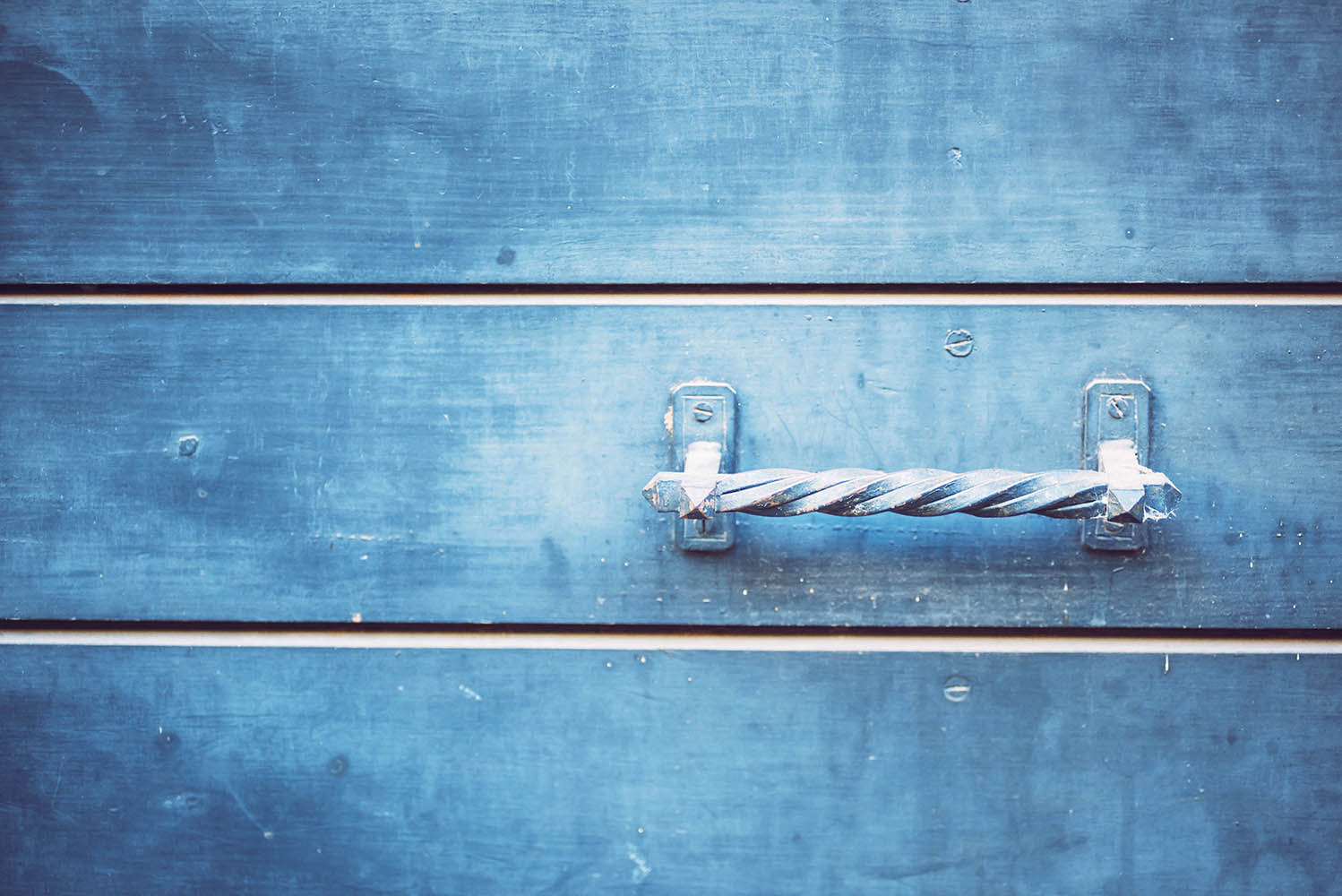 Detail of doors made of wood painted blue. Texture background