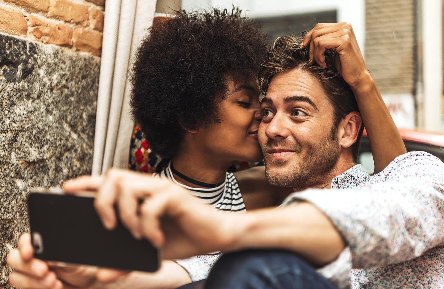 Woman kissing man while taking selfie