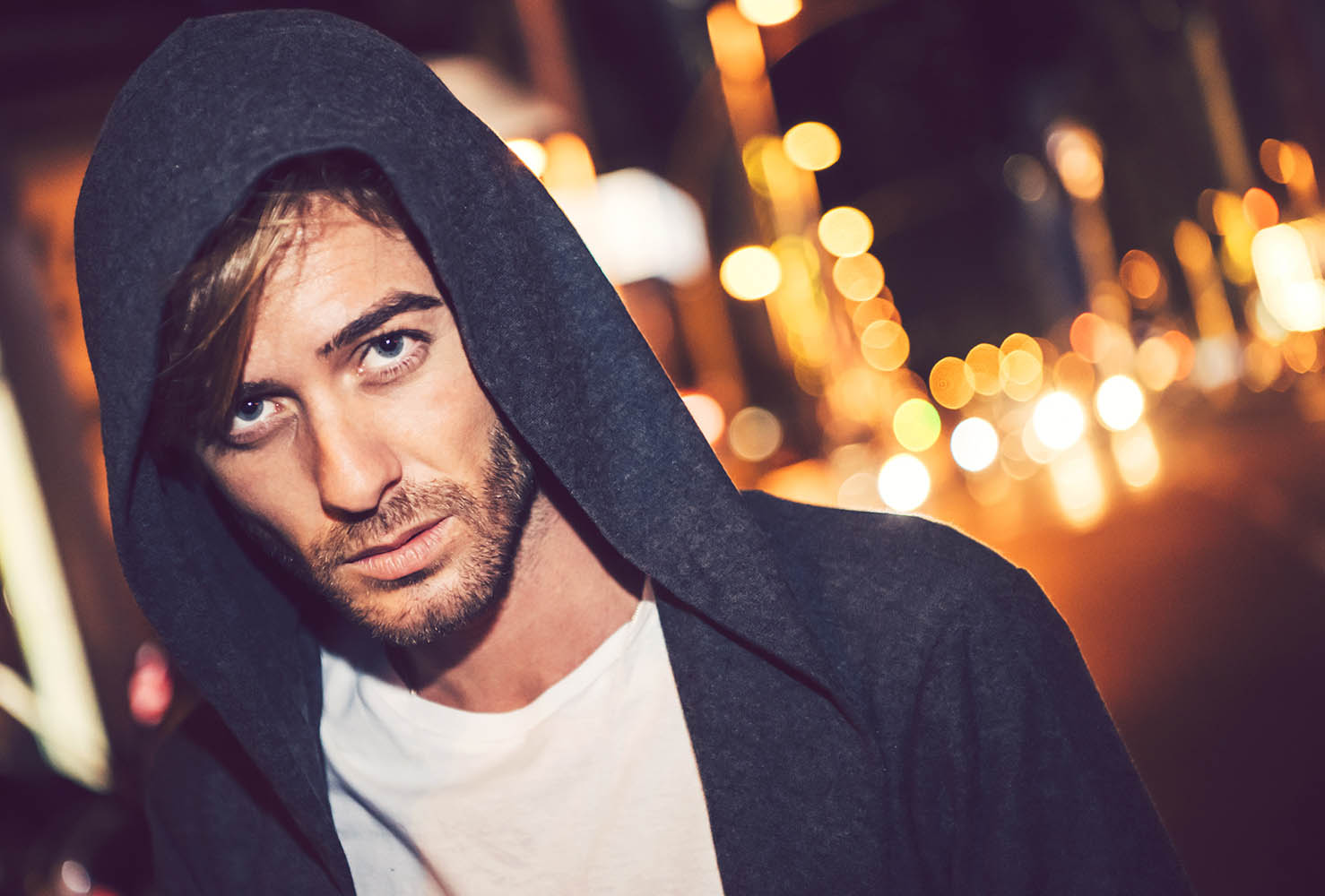 Attractive young caucasian man with hoodie in a city street at n