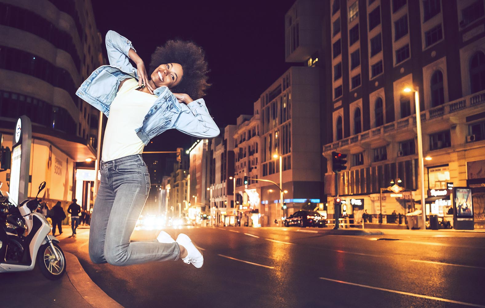 Beautiful young black woman jumping in a city street at night