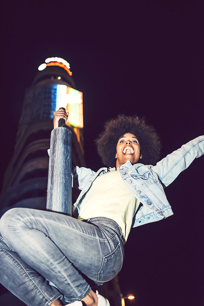 Beautiful black woman perched on a pole partying