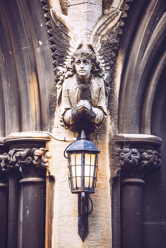 Angels holding lanterns at the arch of a church, located in Lond