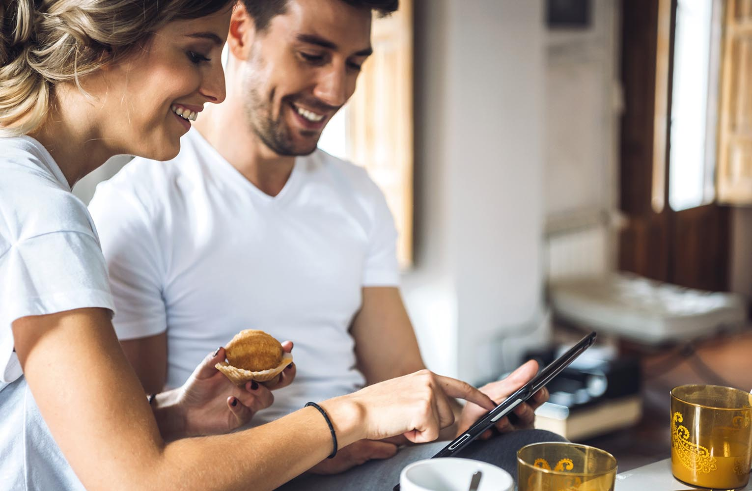 Laughing young couple using tablet at breakfast