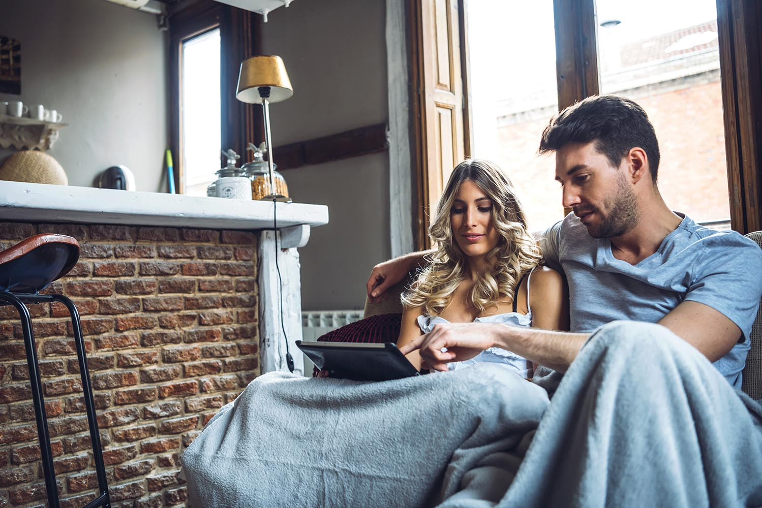 Loving couple sitting at sofa with tablet