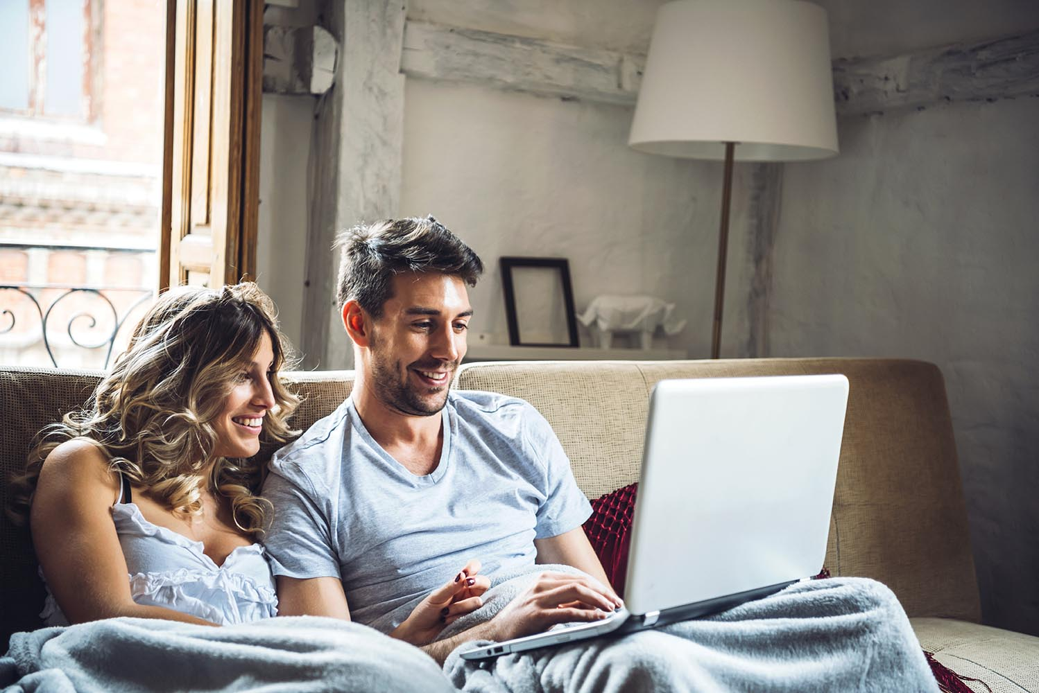 Young smiling couple on sofa with laptop