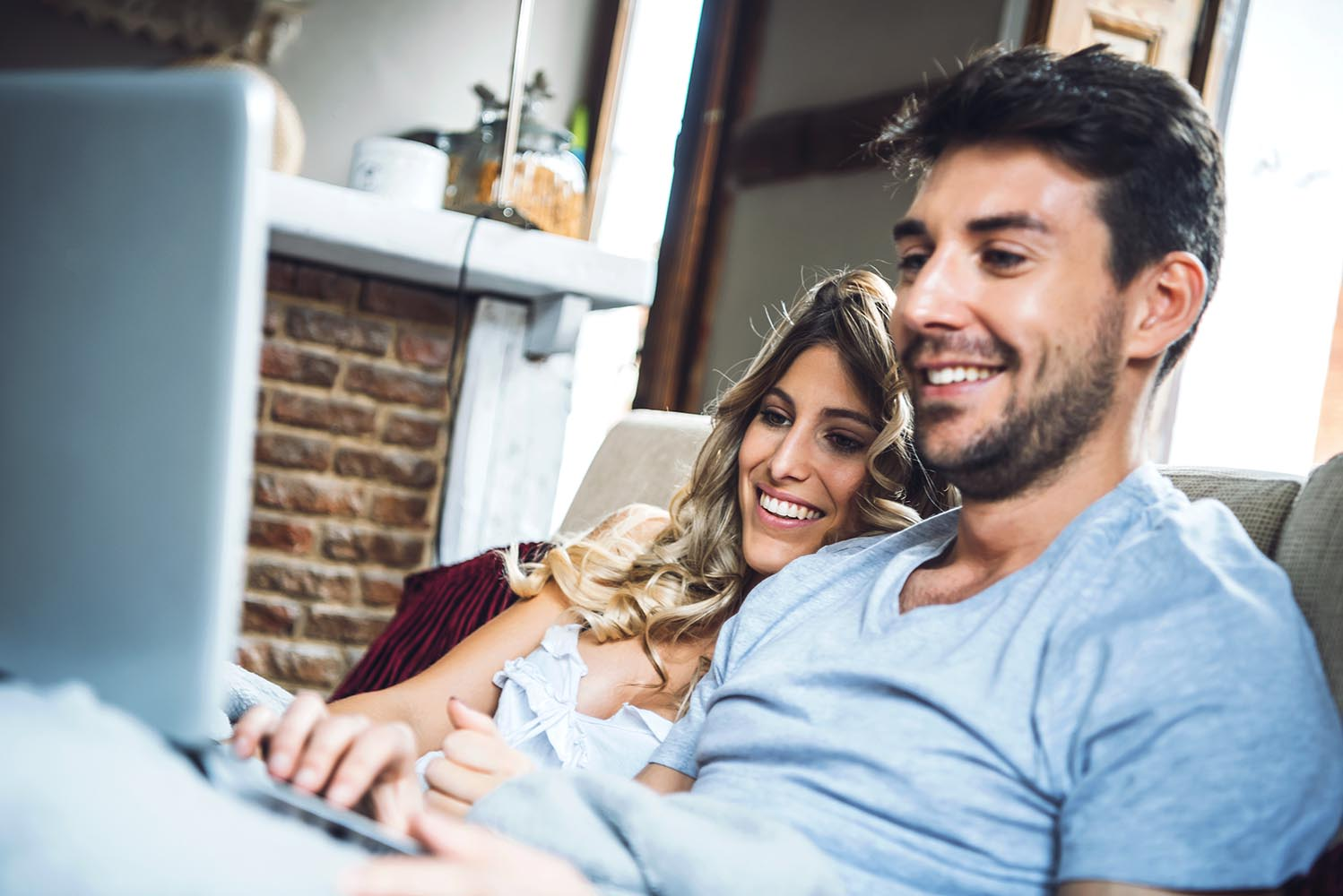 Merry couple on sofa with laptop