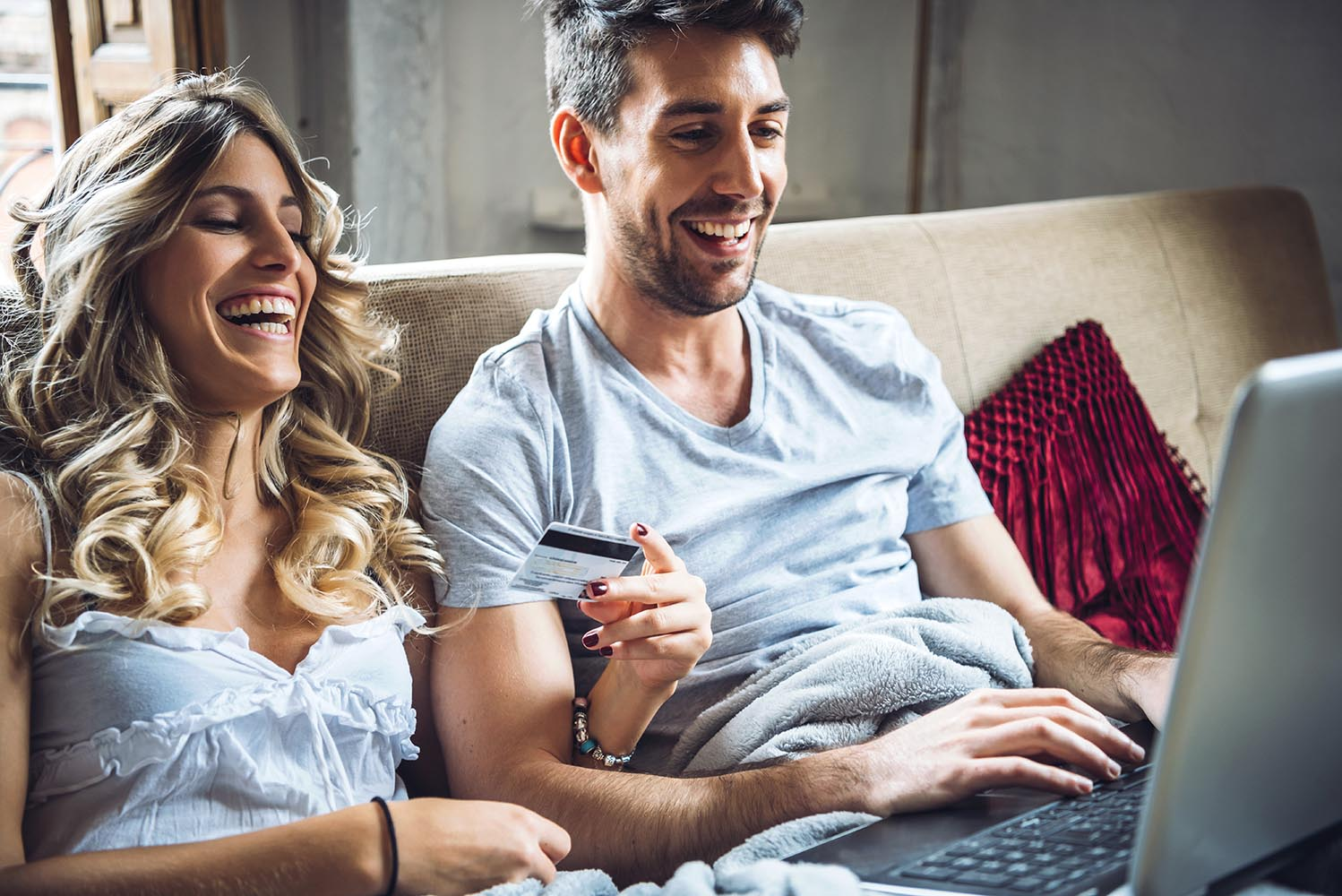 Laughing couple browsing laptop