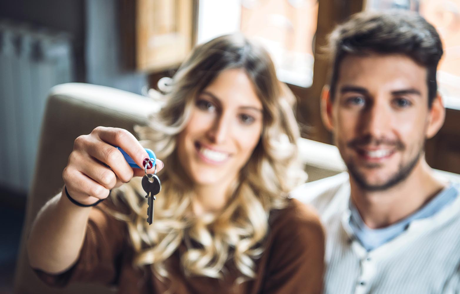 Cheerful couple holding keys from new apartment