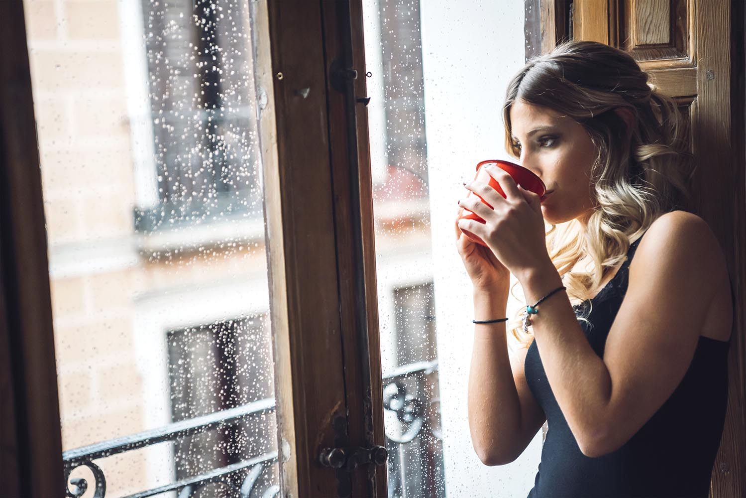 Attractive female drinking and looking at rain
