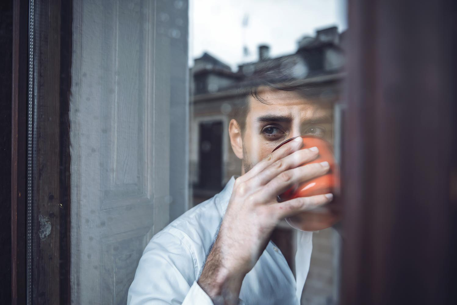 Handsome male drinking tea in rainy day