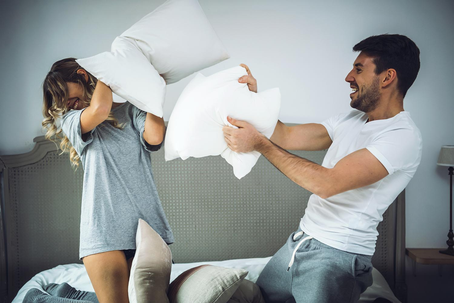 Happy couple fighting with pillows