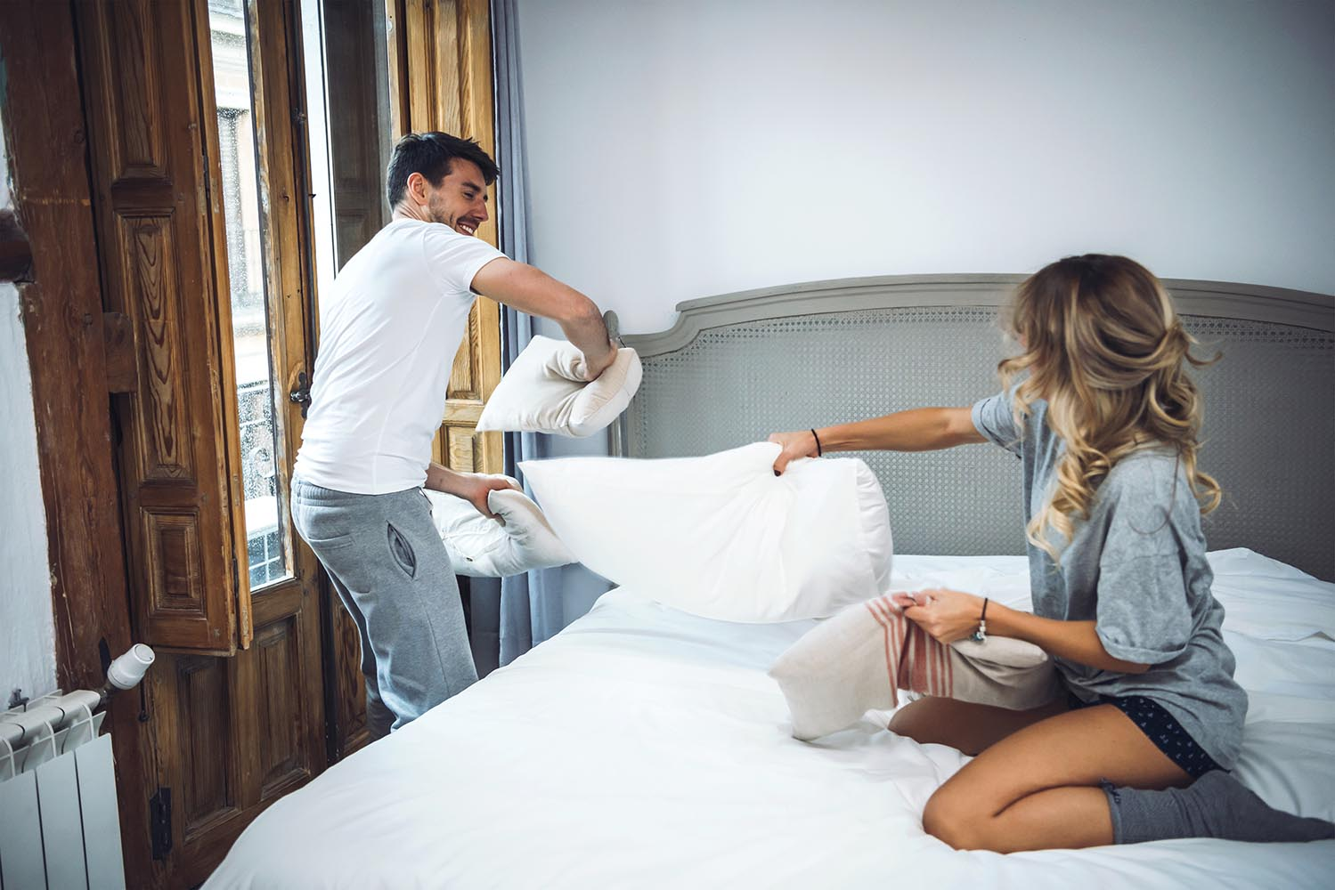 Charming couple pillow fighting