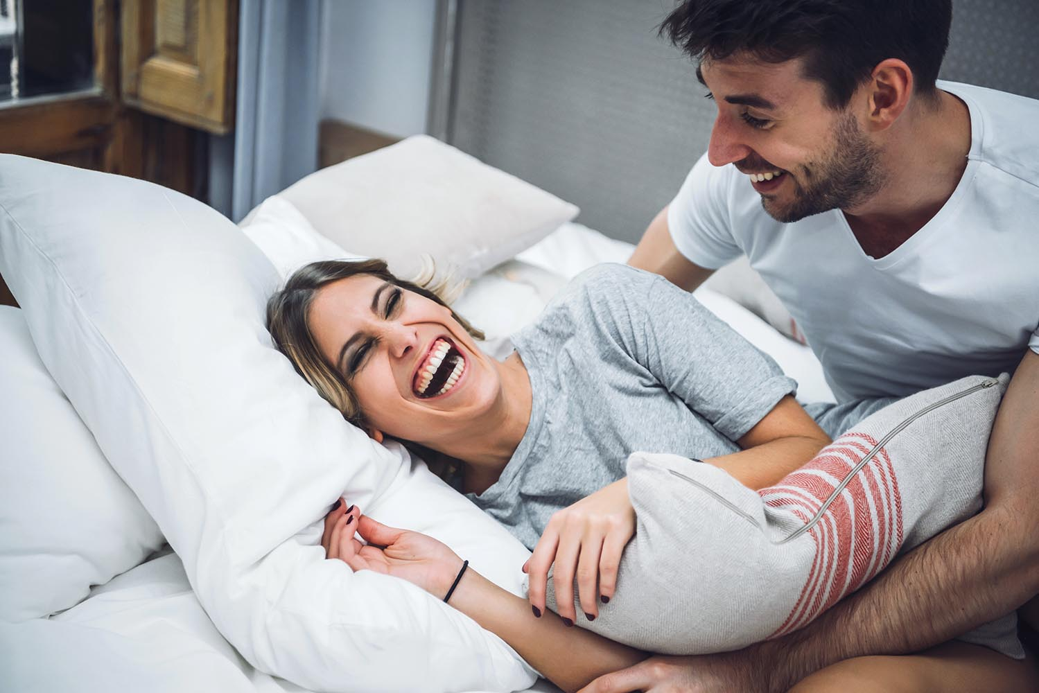 Couple laughing while playing in bed