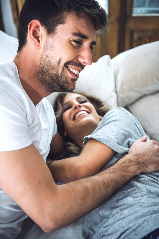 Adorable couple laughing in bed