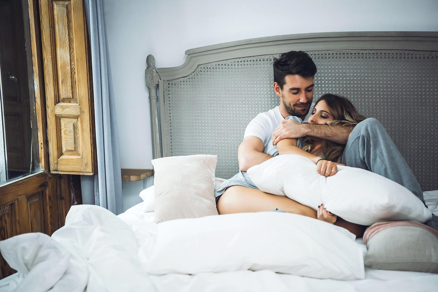 Cheerful couple embracing in bed