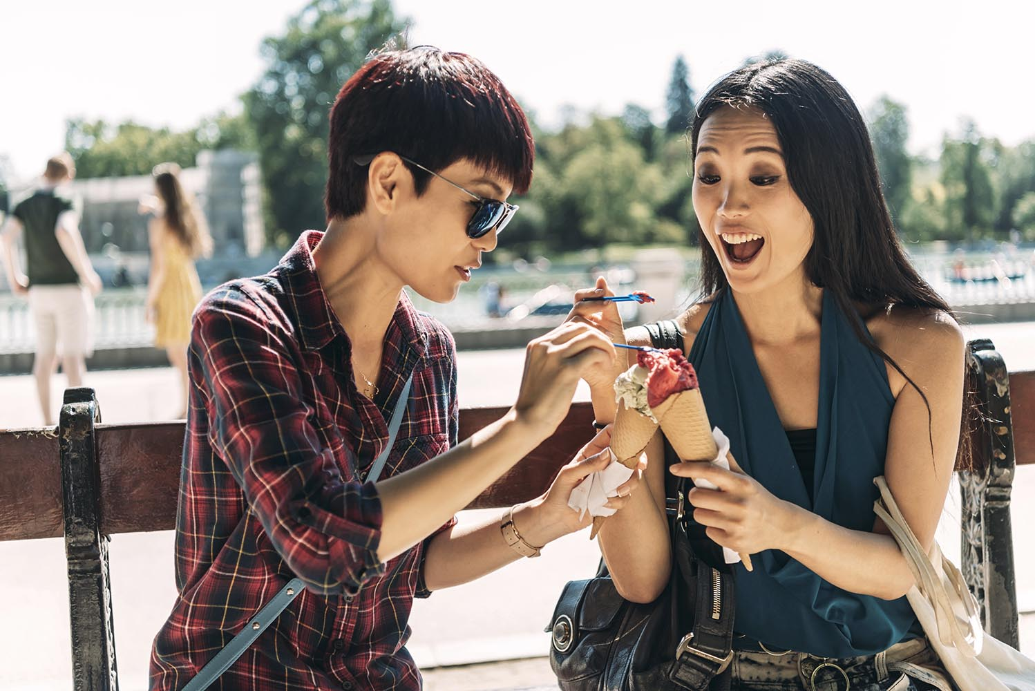 Asian women eating ice cream on park bench