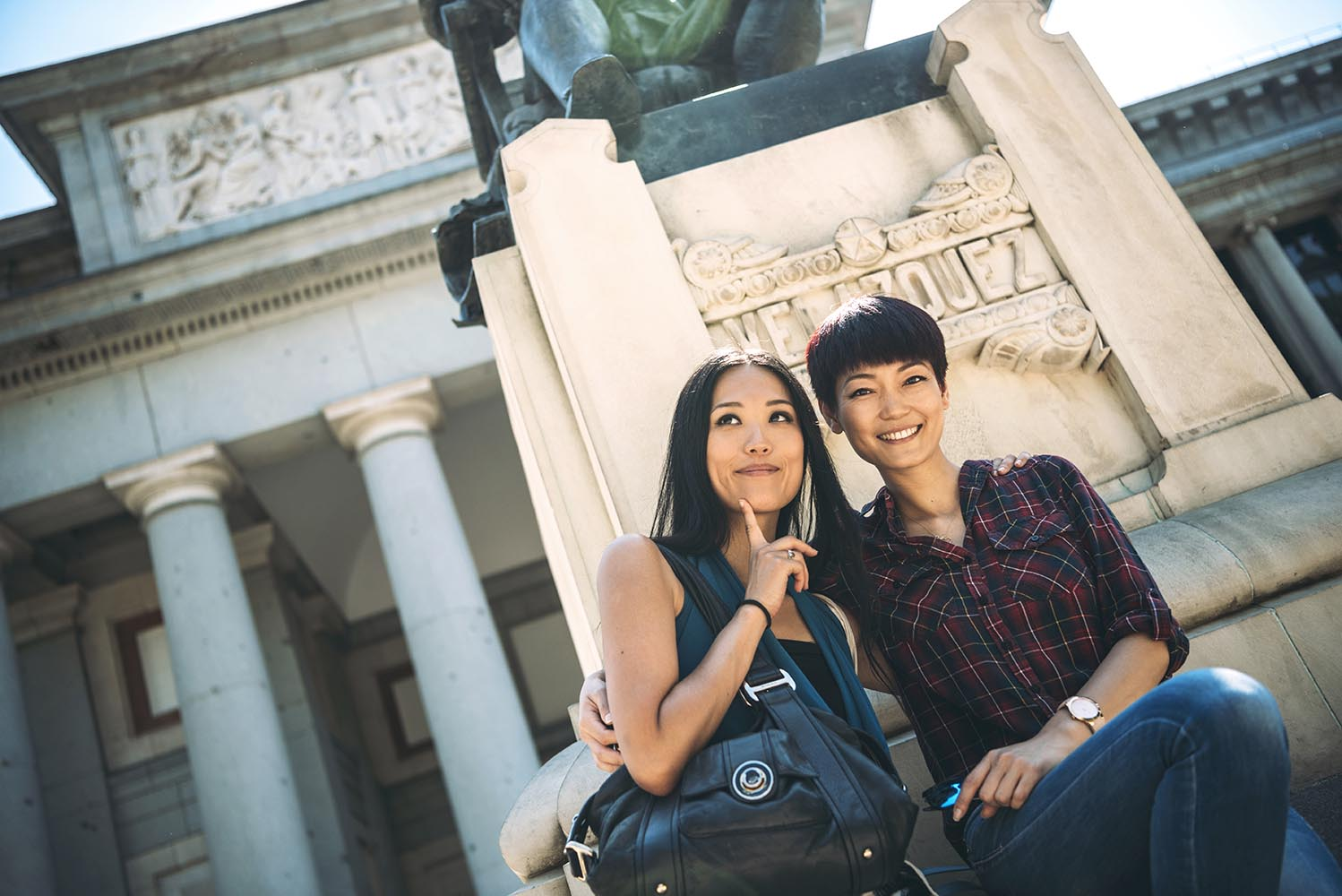Asian female tourists sitting at monument