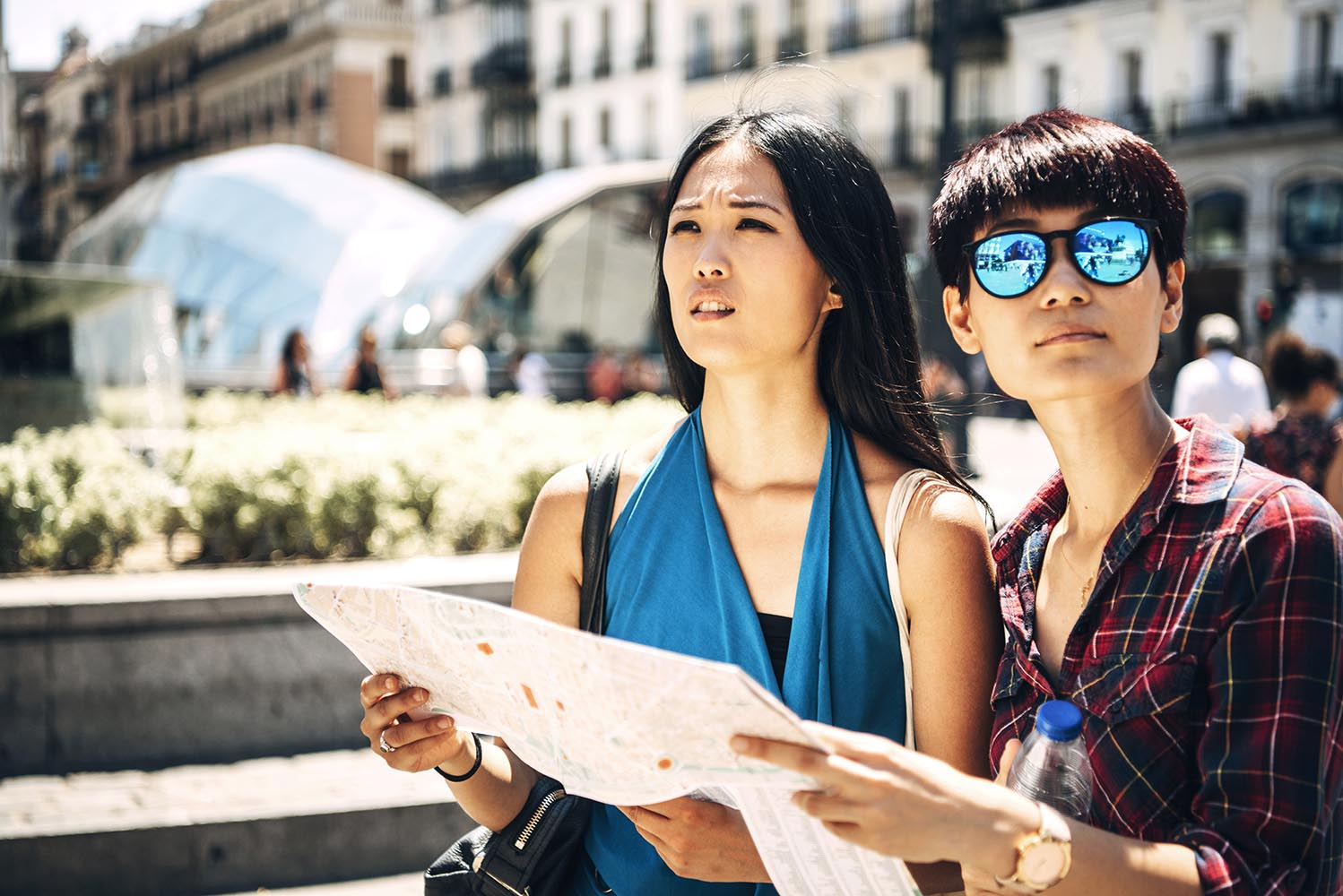 Asian tourist women with map on street