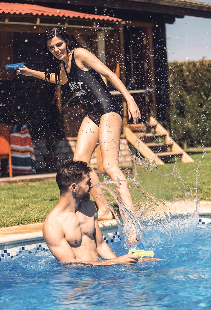 Man and woman splashing in pool