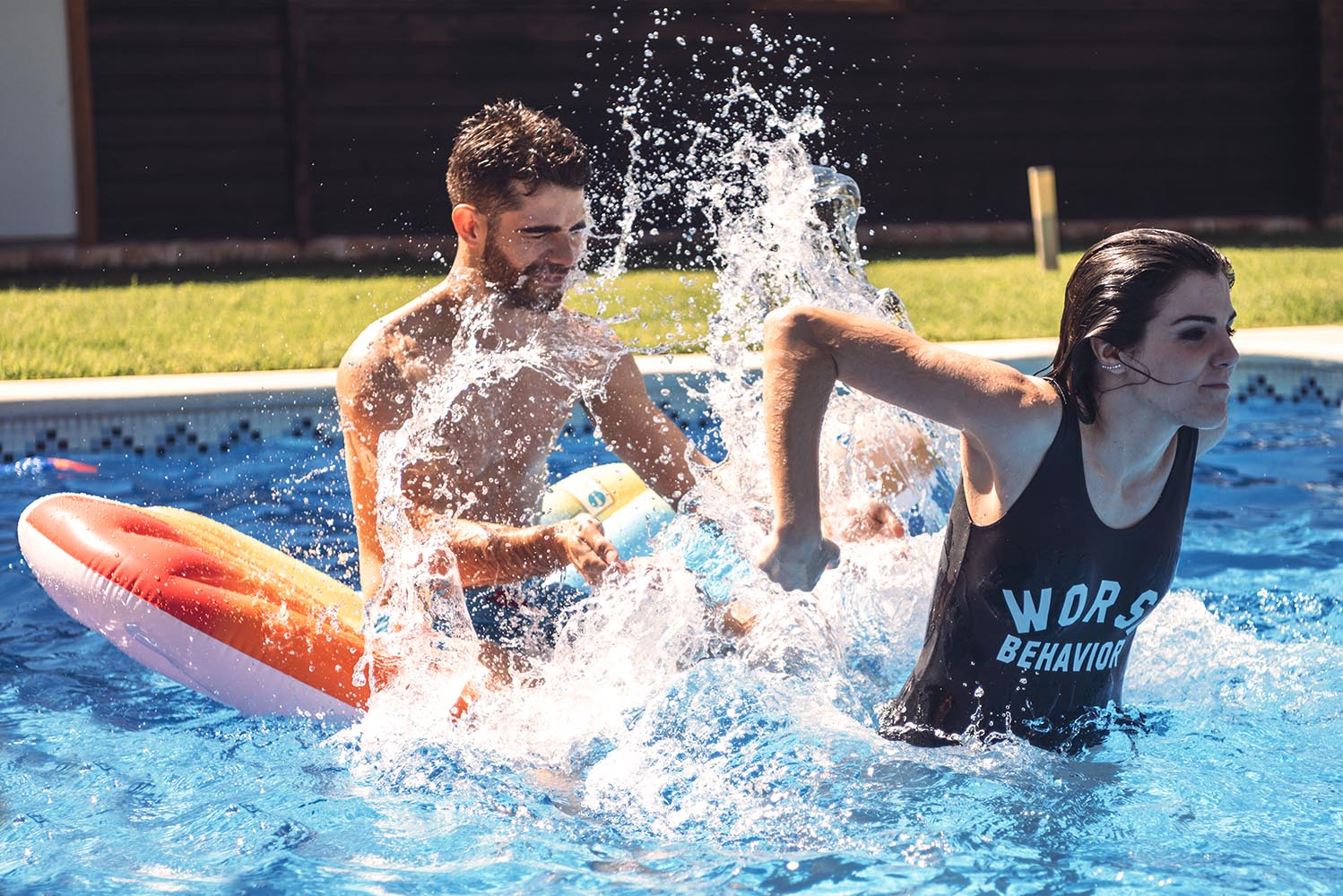 Woman splashing on man in pool