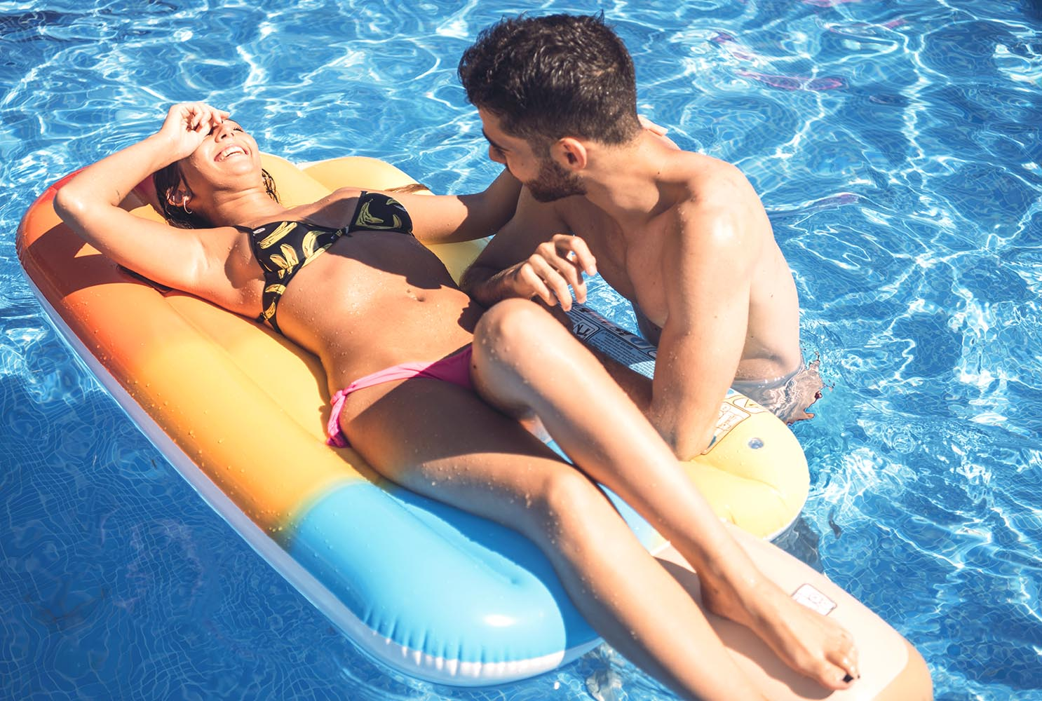 Cheerful girl and man in pool