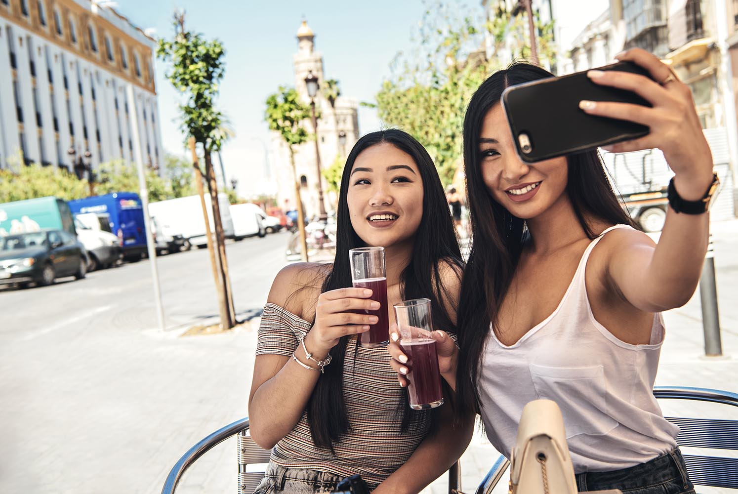 Chinese girls making selfie holding glasses