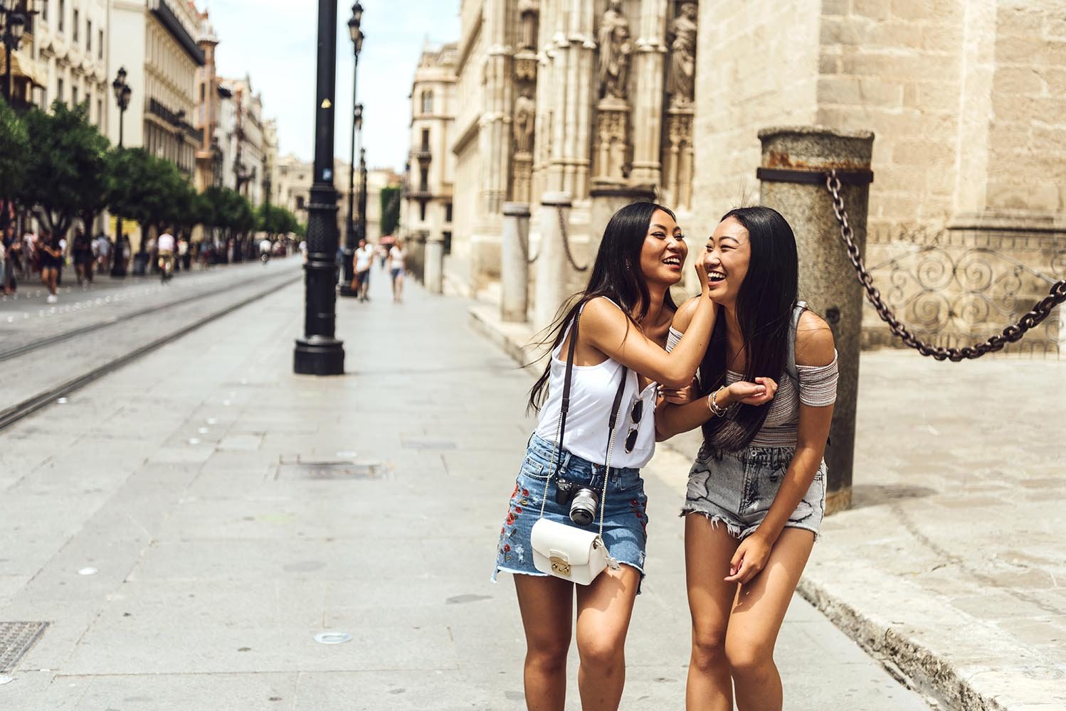 Two Chinese girls walking on street hugging
