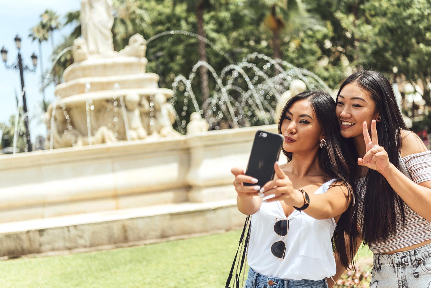 Two Chinese girl taking selfie at fountain