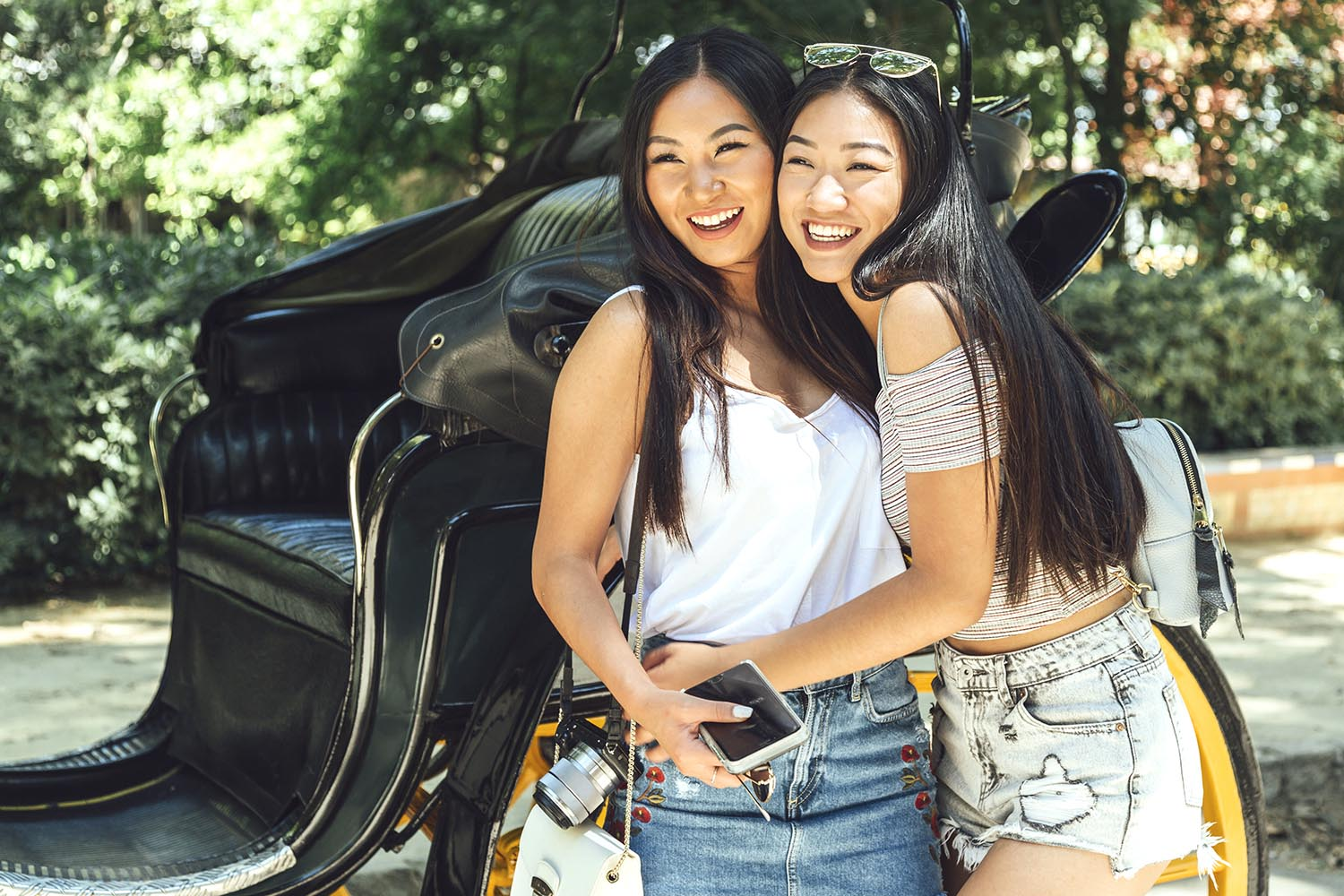 Two Chinese girls standing against carriage